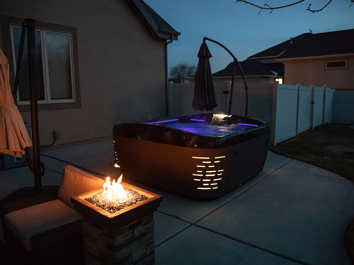 J-585 hot tub with firepit at night